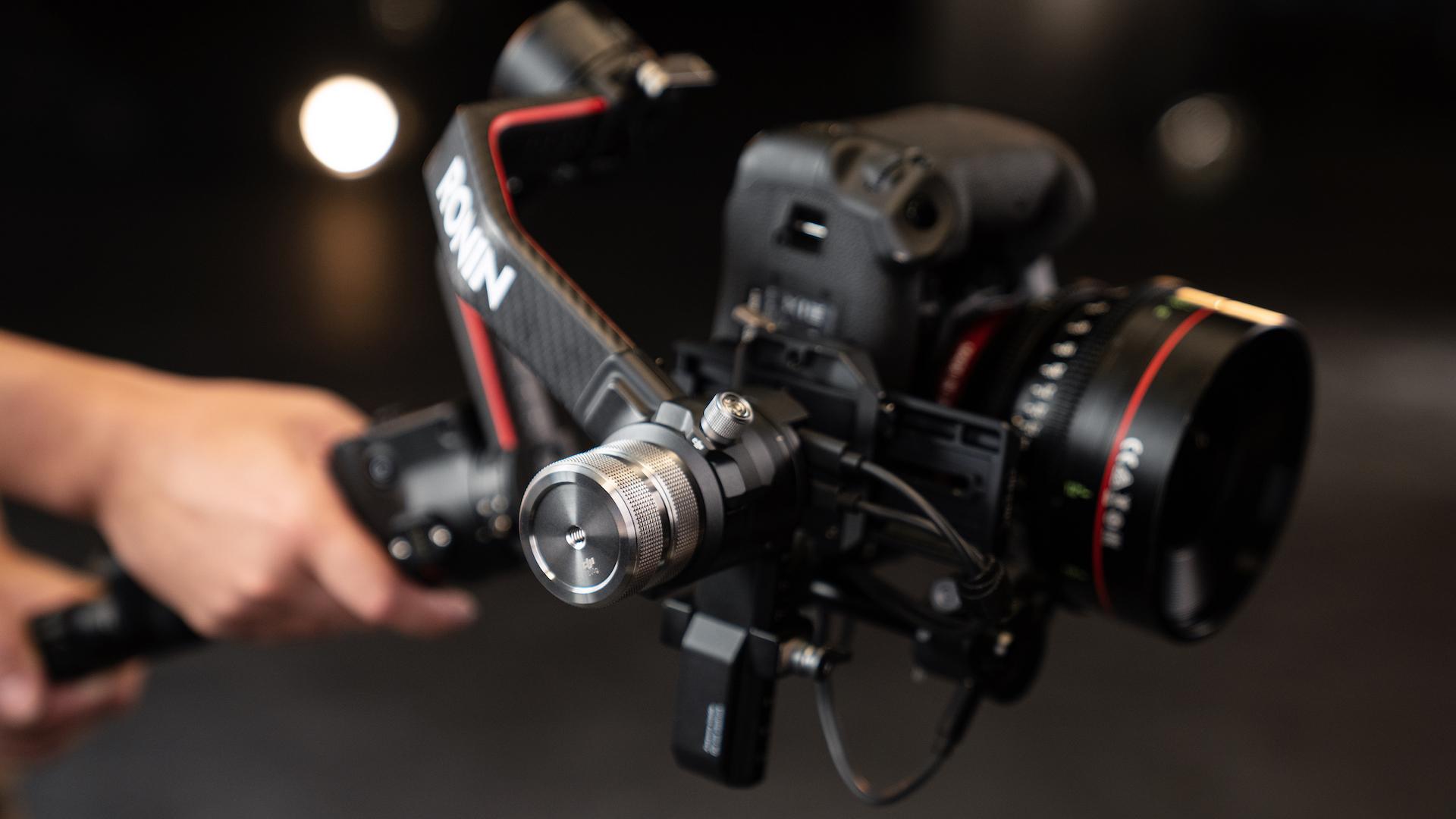 A hand holding the DJI Ronin 2 camera gimbal