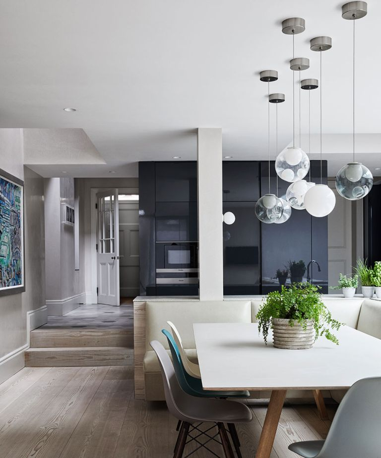 Kitchen lighting ideas showing circular glass pendant lamps over a white dining table and chairs.
