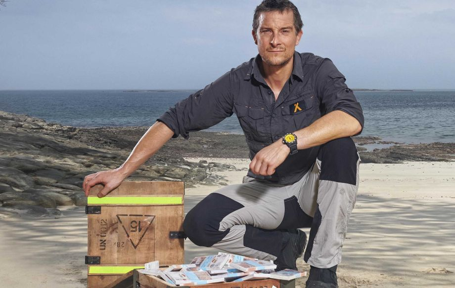 Bear Grylls with a box full of money