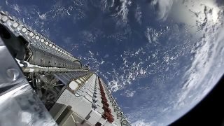 A fleet of SpaceX Starlink internet satellites is seen poised for deployment in orbit in this image from a May 24, 2019 launch.