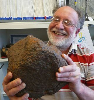 Geochemist Randy Korotev of Washington University in St. Louis holds the meteorite he helped analyze to identify its parent body.