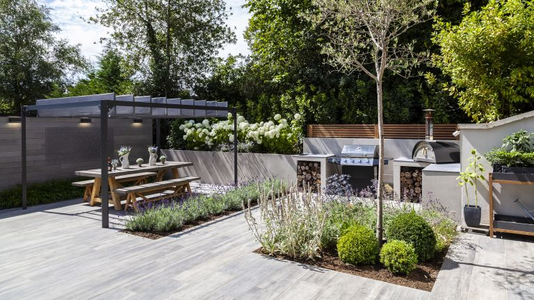 low maintenance landscaping with paving, pergola, outdoor kitchen and pizza oven