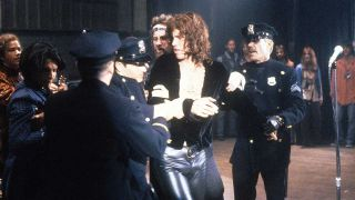 Val Kilmer being apprehended by the police in a scene from the film 'The Doors', 1991
