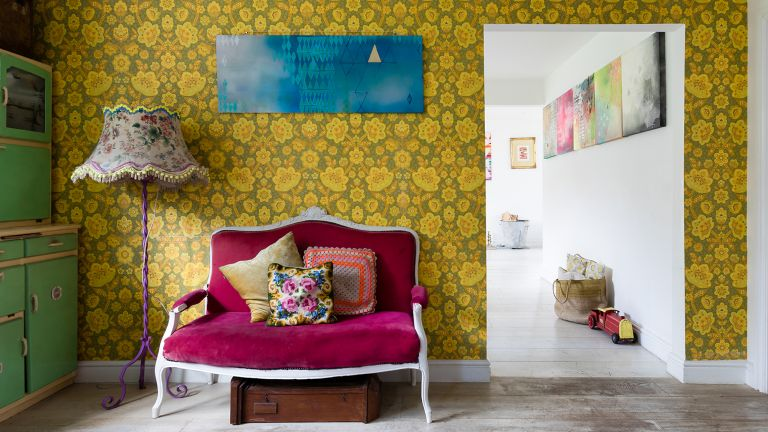 Vintage velvet sofa in front of wall with bold yellow floral wallpaper