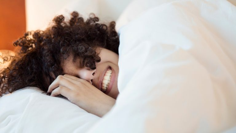 smiling woman in bed under the covers