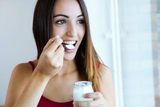 A young woman eats yogurt.