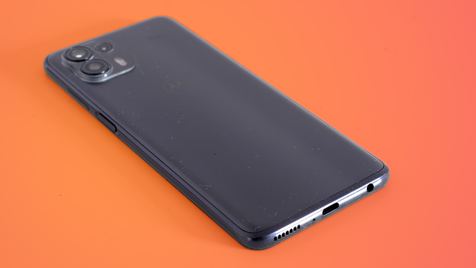 A Motorola Edge 20 Lite from the back on an orange background