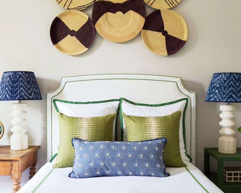 An example of how much should I spend on sheets showing a white bed with green cushions and blue and white bedside lamps