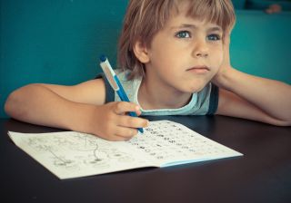 A little boy daydreams while doing his homework