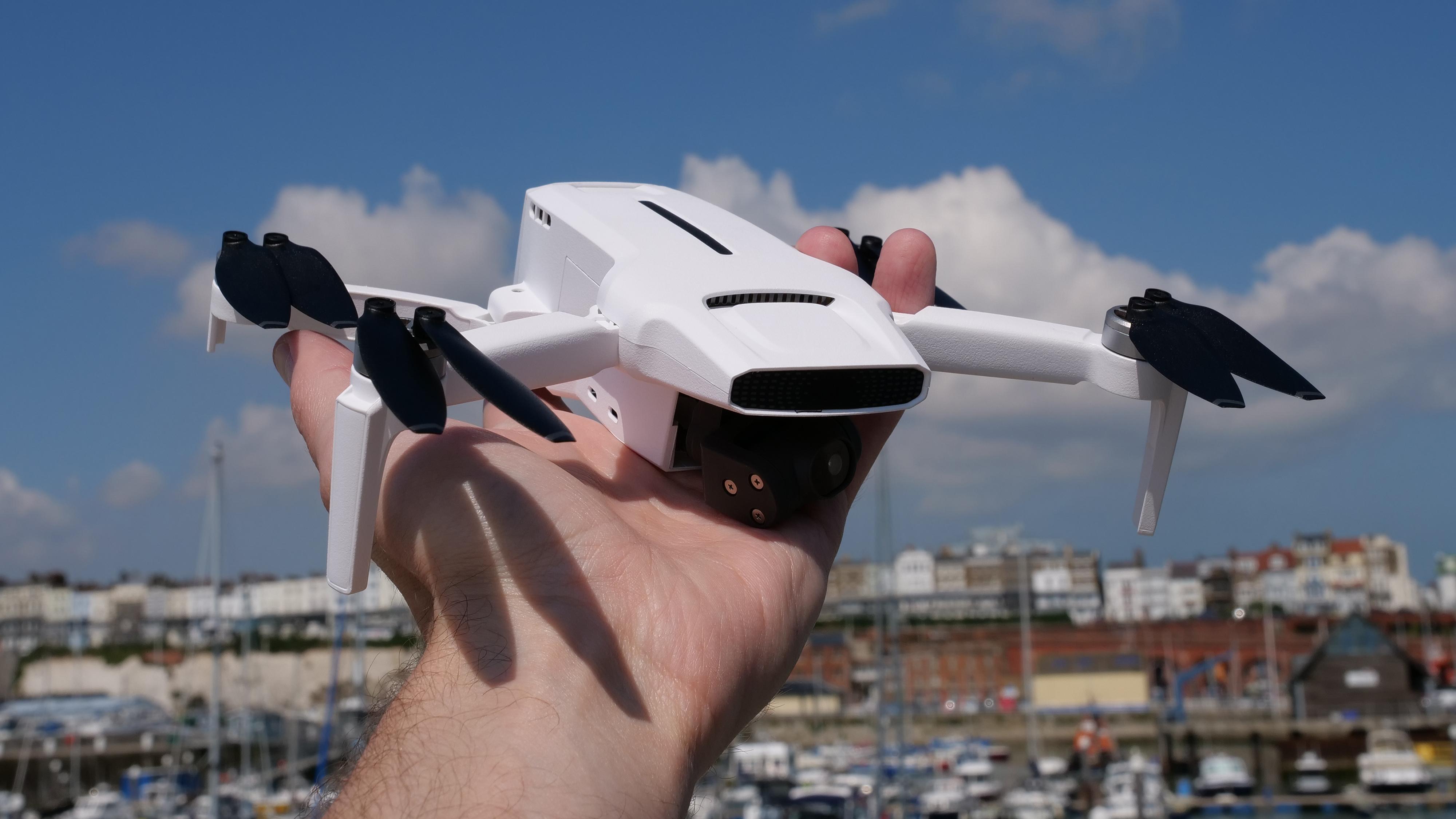 A hand holding the FIMI X8 Mini drone