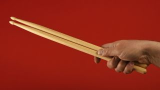 Hand holding a pair of wooden drumsticks on a red background