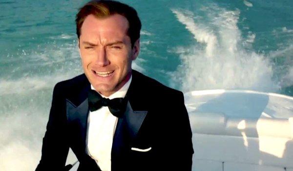 Spy Jude Law rides on a speedboat sharply dressed
