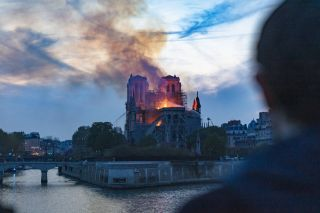an image of Notre Dame burning as a man looks on