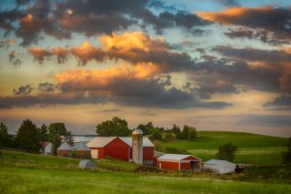 Red barn and other farm buildings nestled in rolling hills