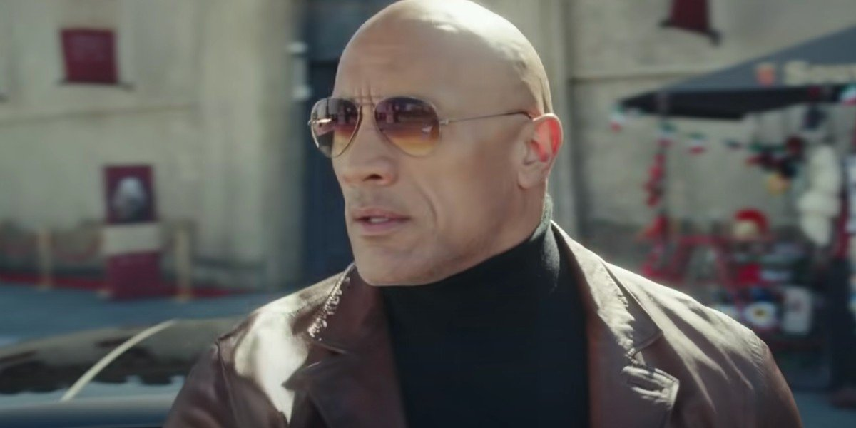 A screenshot from Netflix's Red Notice shows Dwayne Johnson standing in a sunlight museum gallery.