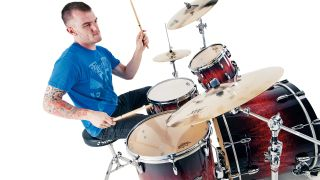 Man with tattoos plays a red acoustic drum kit