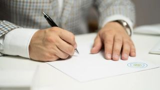 Close up of a person's hands as they sign a document.