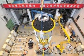 "Work is underway in readying China's thrust into a space station era with Tiangong-1, the first Chinese space station module.. The banner above the hardware reads: ""Carry on the spirit of human spaceflight, insure the complete success of the docking missi"