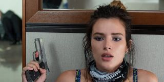 Infamous Bella Thorne hiding behind a wall, holding a gun