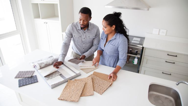 Couple examining fabric swatches in new home - stock photo home renovation