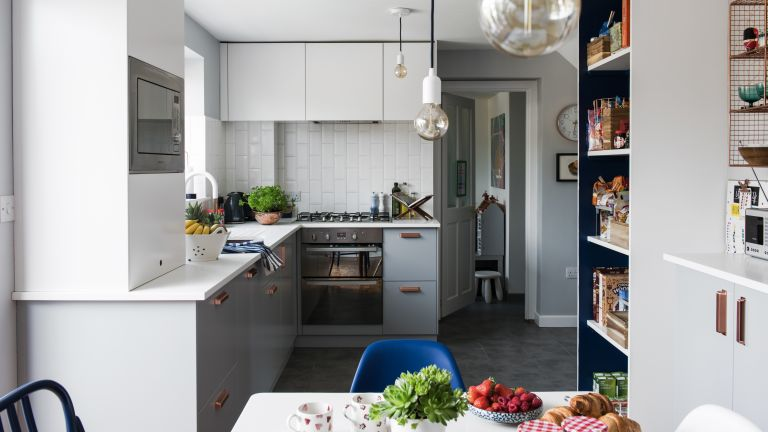 Georgia Broome kitchen: grey and white contemporary kitchen with monochrome pendant lights, white metro tile splashback and grey slate-effect floor