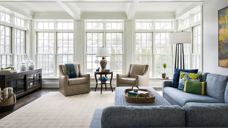 A family room with floor-to-ceiling windows, taupe armchairs and a blue corner sofa