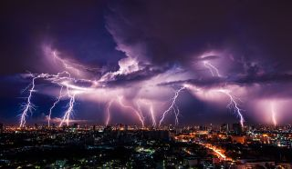 lightning bolts over a city with a purple sky