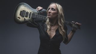 Alice Cooper guitarist Nita Strauss holds her Ibanez guitar over her shoulders