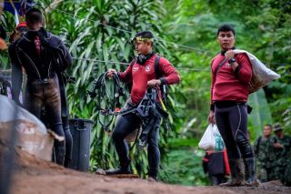 Thai marine police walk out of Tham Luang caves on July 3, 2018, wearing their scuba gear as they continue the rescue operation of 12 boys and their soccer coach who have been stranded for over a week after monsoon rains blocked the main entrance in Chian