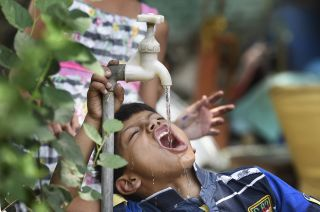 A boy quenches his thirst at a water tap during a scorching heat wave, on May 15, 2017, in New Delhi, India.
