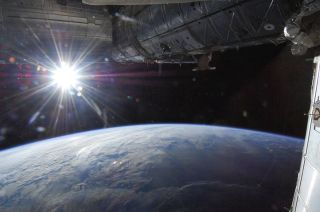 """One of the astronauts of Expedition 36 to the International Space Station took this photo on May 21, 2013. In this view from one of the windows of the orbiting laboratory, the sun shines in a """"starburst"""" mode above Earth's horizon."""