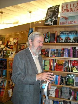 Older gentleman in a grey suit jacket stands in a bookstore giving a lecture.