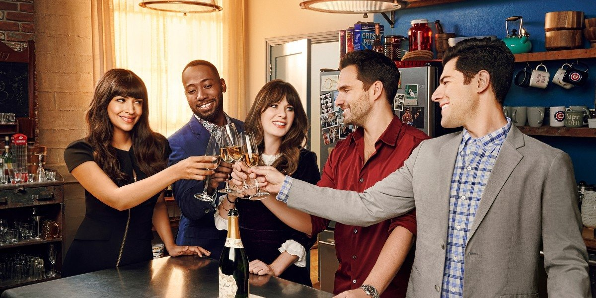 The cast of New Girl in the classic apartment having a toast.