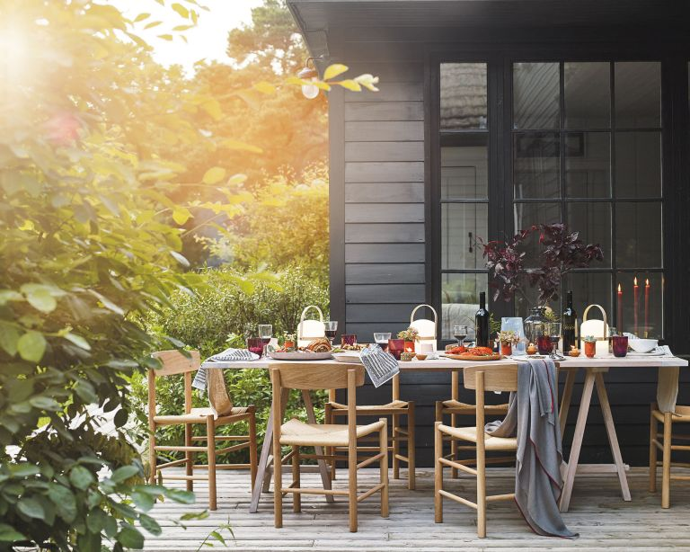 An example of garden party ideas showing a patio area with a dining table in front of a black paneled building
