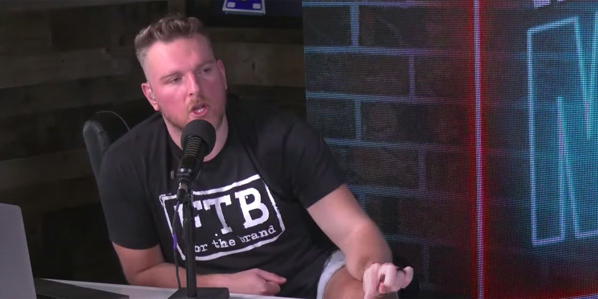 Pat McAfee sitting at a desk with a black shirt on and talking into a microphone.