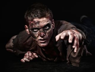A guy dressed up as a zombie with bloody hands and on a black background
