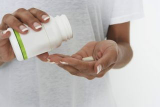 A woman takes a pill from a bottle.