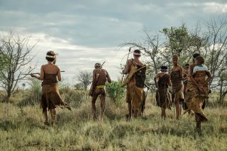 Indigenous San people walk through the landscape in Botswana, Africa.