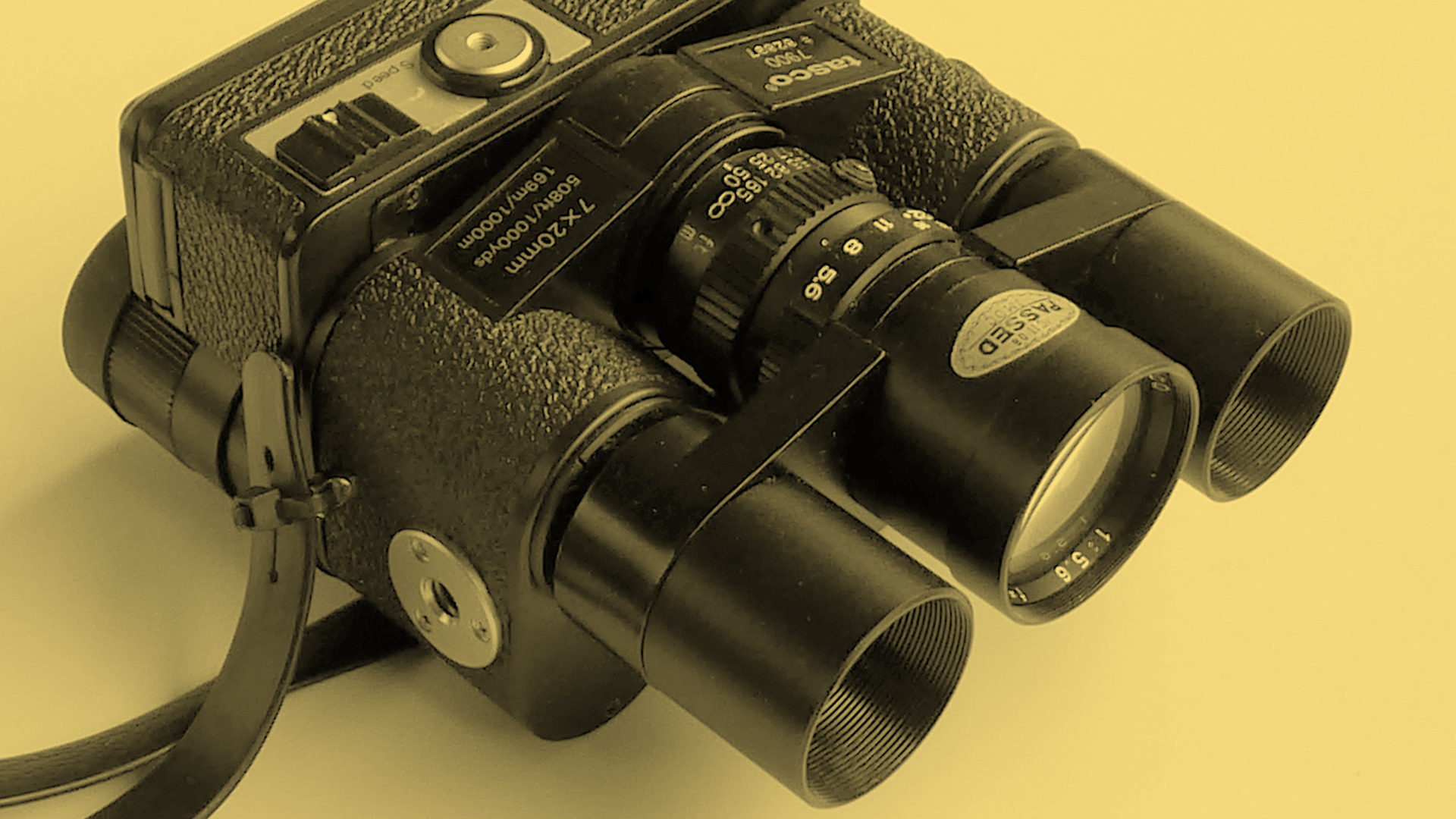 The front of the Tasco 7900 binocular camera on a yellow background