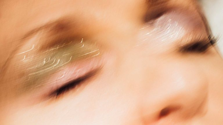 An artfully blurred and stylized image of a close up on someones face with glittery eyeshadow