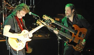 Lee right wields a double neck onstage with Steve Hackett