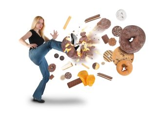 A woman kicks many unhealthy foods away from herself