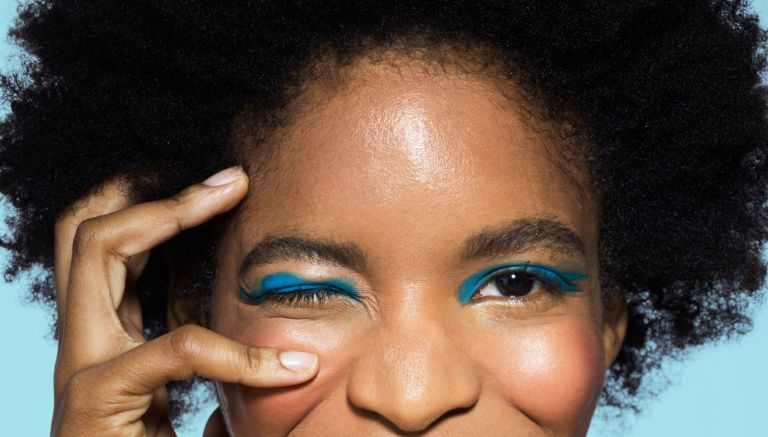 Close-up of young mixed-race woman looking to camera, smiling, wearing blue eye make-up, with hand near eye, with turquoise background