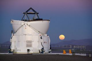 In Chile's Atacama Desert, home of the Paranal Observatory, the moon rises reddishly with one of the four Auxiliary Telescopes standing in the foreground.