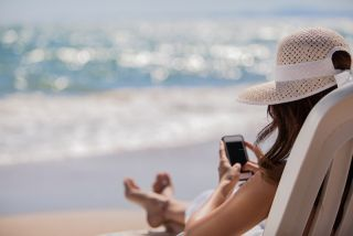 A woman sits on a chair at the beach, wearing a wide-brimmed hat, checking her phone.
