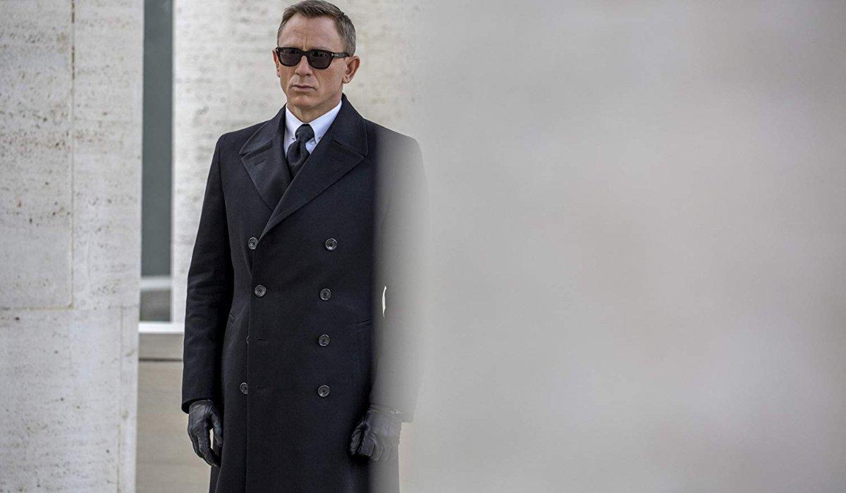 Spectre Bond standing at funeral sunglasses black coat