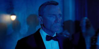 Daniel Craig looks concerned while bathed in blue light in No Time To Die.