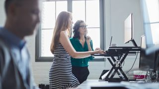 Two woman using one of the best standing desks