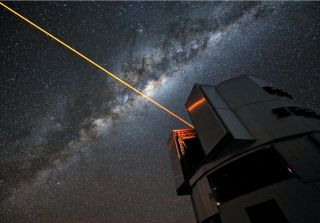 A bright laser beam shines out of the top of a telescope.