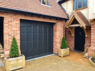 A mock tudor house with a panelled electric garage door